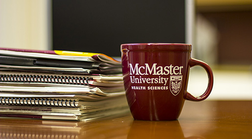McMaster University Health Sciences mug and a stack of papers